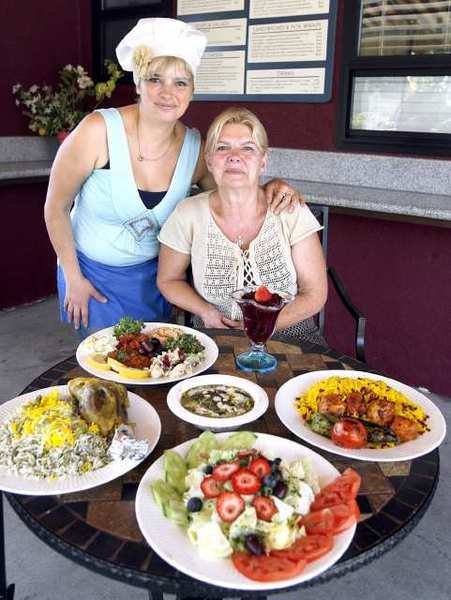 Owners Sonia Race, left, and her mother Zina Race, at Zina's Healthy Corner in La Canada Flintridge. Clockwise from left are lamb shank with fava bean rice, a selection of sides, boneless chicken breast kabob and a salad with fruit.