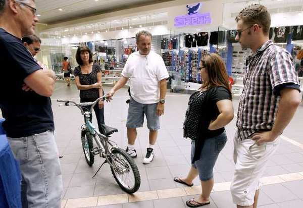 Bike Angels member Rob Wendlandt, center, holds a used bike that Crystal Girone, second from right, and Michael Cozakos, right, donated to the group at the Burbank Town Center. The group hopes to collect about 200 bikes, refurbish them and give them away for Christmas. The group will clean the bikes and replace at least the tires, seat, handles and anything else that needs repair.