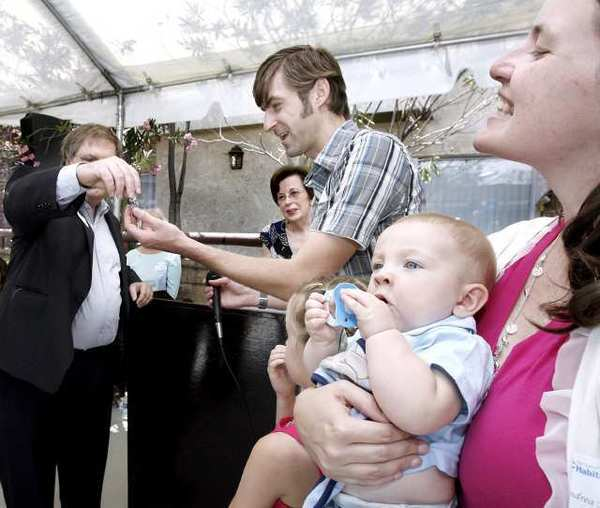 San Gabriel Valley Habitat for Humanity board member Thomas Bunn III, left, hands the keys to their new home to Shane Mulholland as his wife Andrea and baby Luke look on during ceremony for the Geneva Street homes in Glendale.