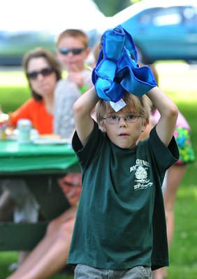 Eric Hofacker, 10, of Bath moves his seat during a pig roast at Cliff Cowling Field as part of the Bath's 275th anniversary on Saturday afternoon. The pig was 260 pounds and donated by Deysher's Custom Butchering located int Bath. The afternoon featured food and music.