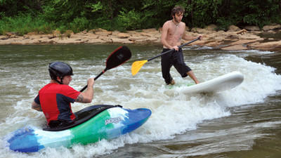 Mike Cook (front) and Rob Mazzetti (back) surf a whitewater rapid on the Stonycreek River near Greenhouse Park.