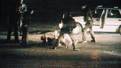 A screenshot of a CBS Television broadcast showing the March 3, 1991, beating of Rodney King by LAPD officers.