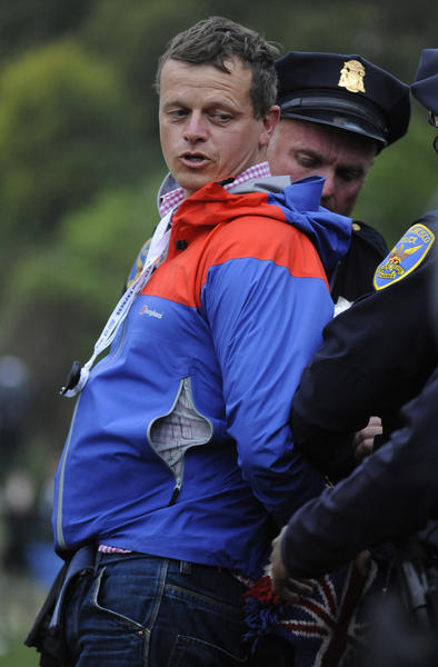 A man is removed after interrupting the trophy ceremony as NBC broadcaster Bob Costas interviews golfer Webb Simpson of the United States, right, after winning the 2012 U.S. Open atThe Olympic Club in San Francisco,