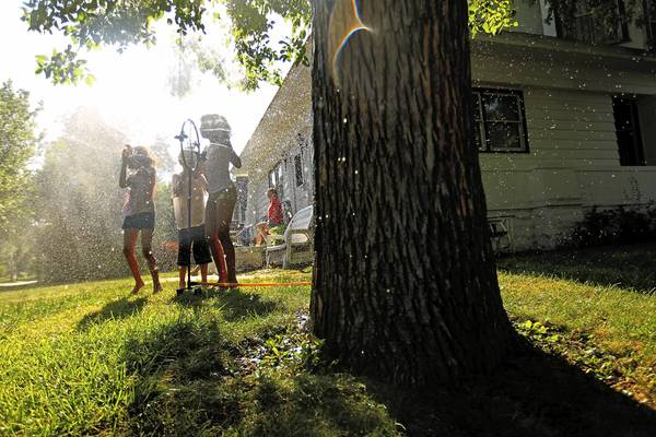 Corenna King, 10, and her siblings, Corenell, 9, and Cayden, 7, cool off in a lawn sprinkler on Western Avenue in Joliet.