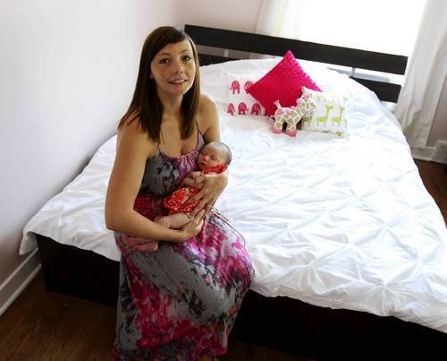 Emma Fox-Lind holds her five week old daughter Sofia Lind in their Glencoe home.