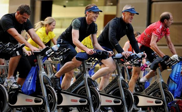 Participants ride exercise bikes during a group outdoor fitness promotion in central Sydney on July 5, 2011.