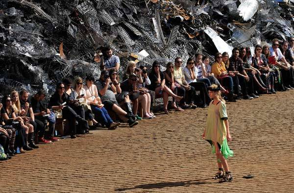 A model presents a creation from the Cavalera Summer 2012/2013 collection at a junkyard, during Sao Paulo Fashion Week.