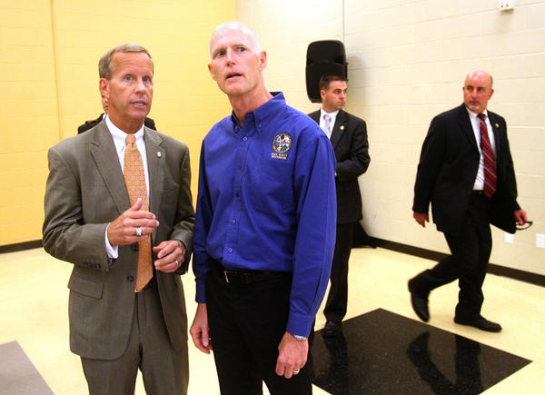 Governor Rick Scott chats with Frank Brogan, Chancellor of the State University System of Florida, before addressing the Board of Governors meeting luncheon, at the University of Central Florida, Tuesday, June 19, 2012.