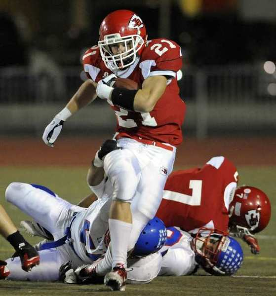 Burroughs' Zander Anding (21) slips through a tackle in the in the first half of a first-round CIF-SS playoff game against Los Altos at Glendale High School in Glendale, Calif., on Friday, Nov. 18, 2011.