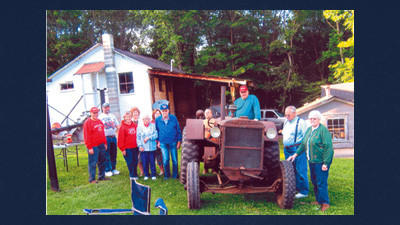 A group of Hillcrest Grangers gather around a vintage Huber tractor at the Matt and Robert Caton country home in Brothersvalley Township June 14 while the group was enjoying a summer evening tour with their neighbors.