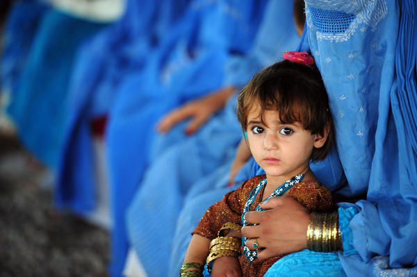 An Afghan girl sits with her mother at The United Nations High Commissioner for Refugees (UNHCR) registration centre on the outskirts of Peshawar on June 19, 2012, as they prepare to return to their home country after fleeing civil war and Taliban rule.