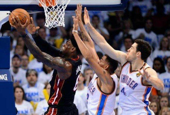 LeBron James of the Miami Heat goes up for a shot against Nick Collison, center, and Thabo Sefolosha, right, of the Oklahoma City Thunder in Game 2 of the NBA Finals.