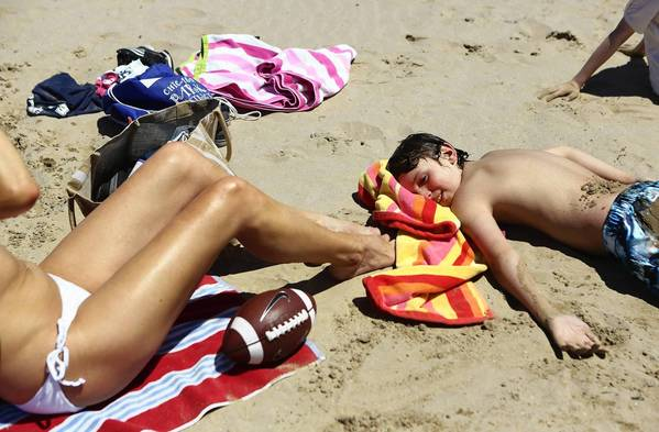 Andrea Galdabini, left, and son, Vincent Galdabini, 12, sunbath at Montrose Beach, but not without applying high-SPF sunscreen.