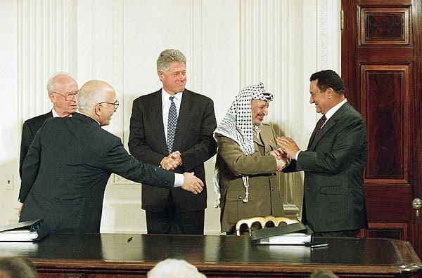 President Clinton looks on as Egyptian President Hosni Mubarak greets Palestinian leader Yasser Arafat at the White House on Sept. 28, 1995, after the signing of a historic Middle East accord. With them are Israeli Prime Minister Yitzhak Rabin, far left, and King Hussein of Jordan.