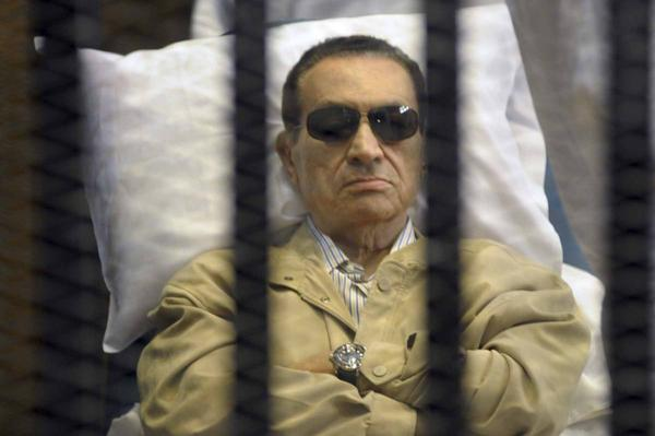 In this June 2 file photo, Egypt's ex-President Hosni Mubarak lays on a gurney inside a barred cage in the police academy courthouse in Cairo, Egypt. A security official says Egypt's ousted leader has been put on life support after his heart stopped as he arrived at a military hospital.