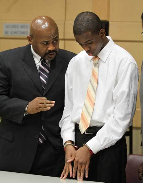 Defense attorney Johnny McCray, Jr. talks to his client,  Matthew Bent after he was found guilty of aggravated battery for his part in the burning of Michael Brewer.