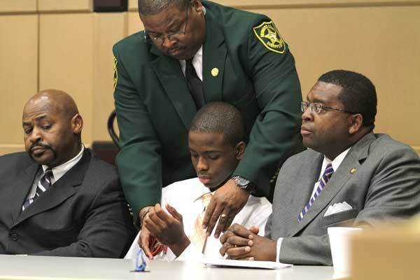 Defense attorney Johnny McCray, Jr. looks on as his client,  Matthew Bent is handcuffed by a court deputy  after he was found guilty of aggravated battery for his part in the burning of Michael Brewer. On the right is attorney Perry Thurston who also represent Bent.