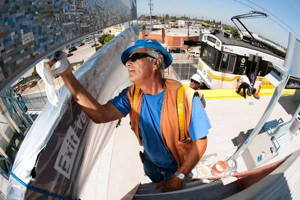 Metro contractor Alfred Lopez of California Neon Products spruces up artwork and signage at the Expo Line's Culver City station in advance of its official opening.