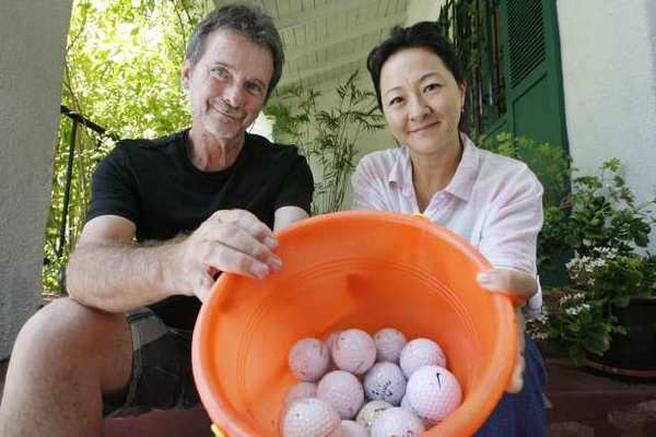 Neighbors Edward Bash and Suzie Nelson hold a bucket of golf balls that have been hit from Oakmont Country Club onto their side of the street.