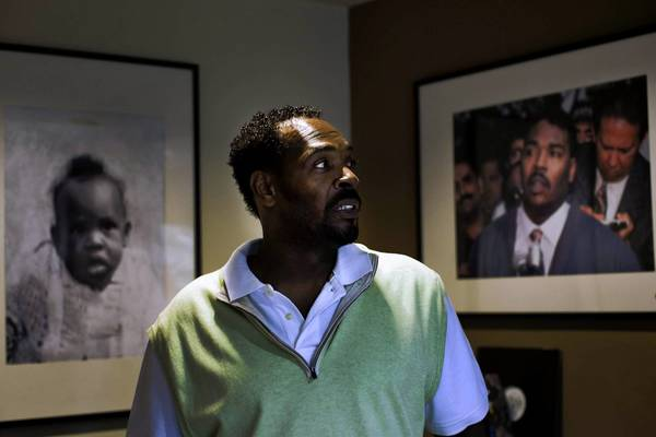 Rodney King poses with a picture of himself that hangs in his home, taken in 1992.