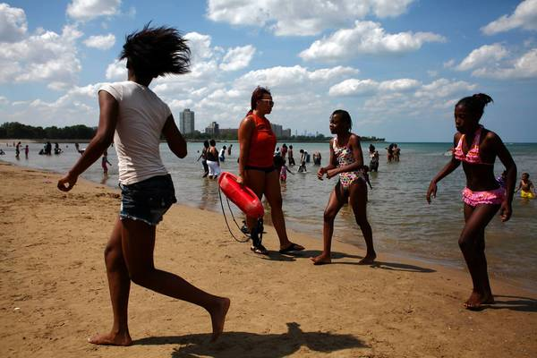 A lifeguard watches over swimmers at 63rd Street Beach in Chicago on Tuesday. State guidelines say where lifeguards are required, there must be a minimum of one per 100 bathers or 2,000 square feet of water surface area.