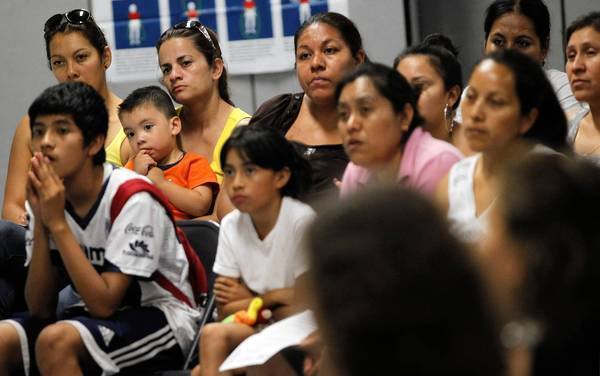 People attend an informational meeting Tuesday, sponsored by the United Neighborhood Organization, about President Barack Obama's new federal immigration policy. The shift would relax rules covering undocumented immigrants who were brought to this country as young children.