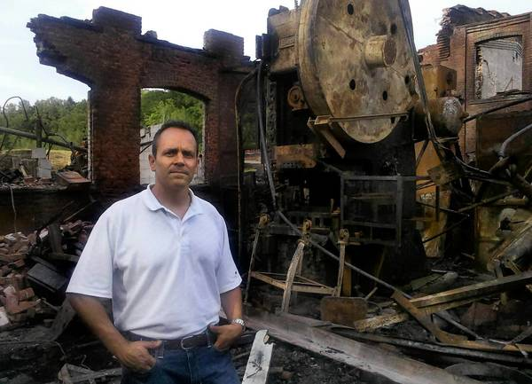 Matt Bevin, 6th generation owner of the Bevin Bros. Bell Company in East Hampton, stands near the 150 ton press that was the companies largest press. Visit courant.com/bevinbell for photos, video and previous coverage.