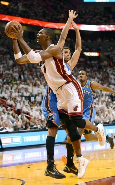 Miami Heat power forward Chris Bosh (1) drives to the basket past Oklahoma City Thunder shooting guard Thabo Sefolosha (2) during the fourth quarter of game four in the 2012 NBA Finals at the American Airlines Arena.
