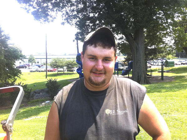Smithsburg resident Joel Reynolds, 21, takes a break Wednesday from cutting grass in the heat at Staley Park.