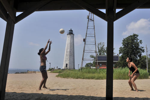 Susanna Lincoln, left, 18, and Tiffany Ayala, 18, both of New Haven play volleyball on the beach at Lighthouse Point Park in New Haven Wednesday. Both graduated from Wilbur Cross High School in New Haven Tuesday.
