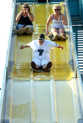 (L to R) Lori Kostro; her son, Cody, 17 and Saige Briner, 16, all of Breinigsville, ride the giant slide at the 29th Annual Schnecksville Fair on Wednesday.
