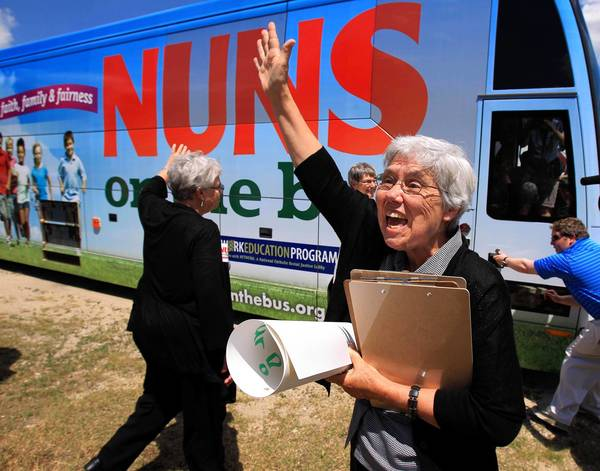 Sister Mary Wendlen waves to supporters Wednesday in Fox Lake, where she and three other nuns visited the headquarters of Republican U.S. Rep. Joe Walsh, to scold Walsh for voting on a House budget the sisters say threatens to hurt the people they serve.