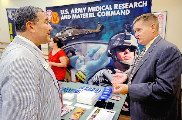 Jim Romano, left, president of the Fort Detrick Alliance, talks Wednesday afternoon with Steve Rountree, acting director of strategic partnership with the U.S. Army Medical Research and Materiel Command, during the Fort Detrick Alliance Expo at Hagerstown Community College's Student Center.