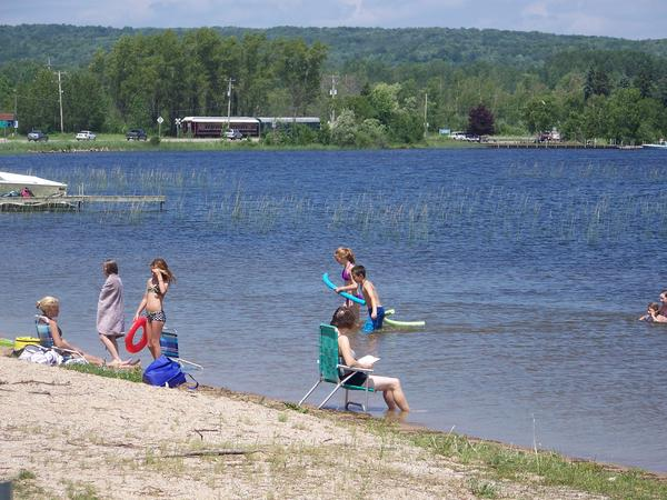 Swimmers take a break from Wednesday's high temperatures with a swim in Crooked Lake, north of Petoskey. While the water may be refreshing, the warm weather could also trigger swimmer's itch in area lakes.