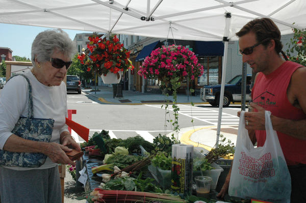Joan Keller (left), a Wequetonsing summer resident, buys produce from Jimmy Spencer, one of the owners of Pond Hill Farm in Harbor Springs.
