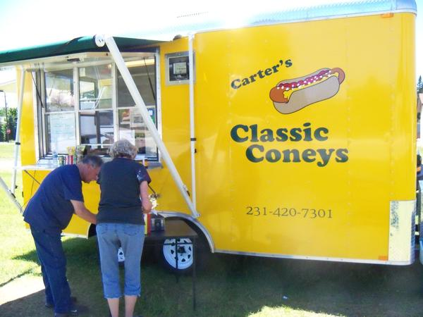 Customers add condiments to their hot dogs outside Carter's Classic Coney's, a trailer-based business that recently opened in Pellston.