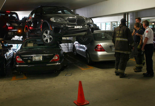Firefighters make plans to remove an Enterprise BMW rental car from the roof of a Jaguar and Mercedes after the driver lost control and went over the railing in the self-park parking garage on 20 E. Randoph in Chicago.