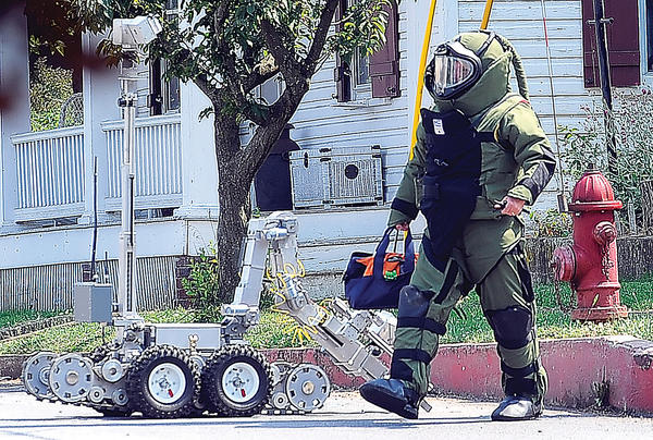 Senior Deputy State Fire Marshal Ed Ernst walks away with a fake pipe bomb Thursday afternoon after it was disrupted by a bomb squad robot on South Mechanic Street in Sharpsburg.