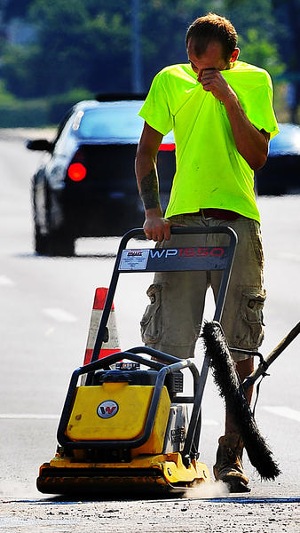 Nigel Reeder wipes his eye Thursday morning while tamping hot asphalt at a new turn lane on Edgewood Drive at Howell Road. The mid-morning temperature was already 90 degrees.