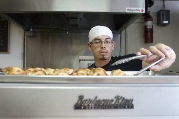 Chef Brian Coronel stocks up some empanadas in a warm oven at World Empanadas in Burbank.