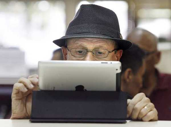 Jeremiah Comey, of Glendale, writes notes on his iPad to remember the information he was given to connect his tablet to the Glendale Central Library. The library's new 3M Cloud technology allows patrons to borrow ebooks.