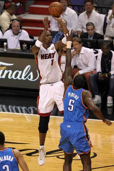 Miami Heat power forward Chris Bosh (1) shoots against Oklahoma City Thunder center Kendrick Perkins (5) during the first quarter in game five in the 2012 NBA Finals at the American Airlines Arena.