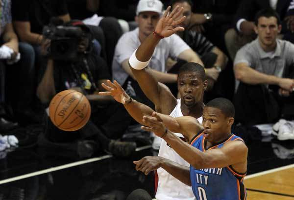 Oklahoma City Thunder point guard Russell Westbrook (0) passes the ball against Miami Heat power forward Chris Bosh (1) during the first quarter in game five in the 2012 NBA Finals at the American Airlines Arena.