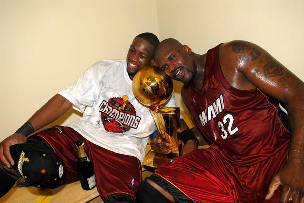 Dwyane Wade, left, and Shaquille O'Neal relish the NBA championship trophy after beating the host Mavericks 95-92 to eliminate Dallas in six games.