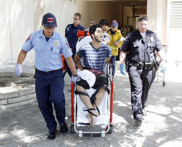 Robert William White, tied and handcuffed on a stair chair, yells the word of God to onlookers as he is wheeled out of an apartment he barricaded himself in after allegedly assaulting a 77-year-old woman with a shovel on Spazier Avenue.