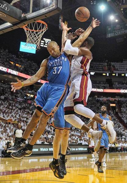 Miami Heat guard Dwyane Wade is fouled by Oklahoma City Thunder guard Derek Fisher during the second quarter of Game 5 of the NBA Finals, Thursday, June 21, 2012 at AmericanAirlines Arena.
