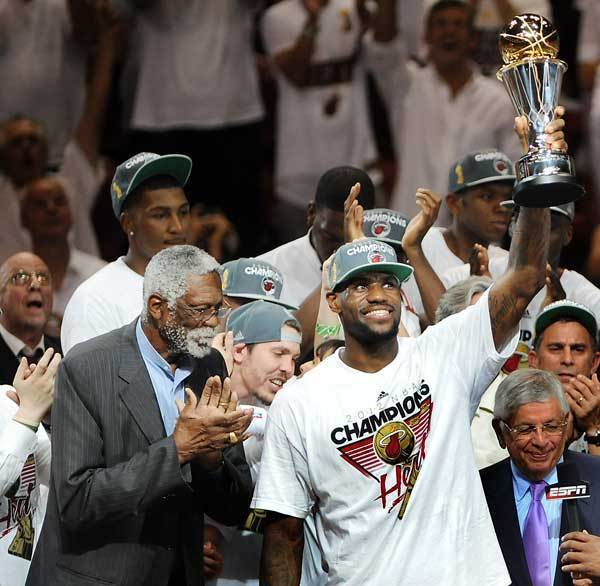 LeBron James hoists the Bill Russell MVP trophy as Bill Russell lookson at left.