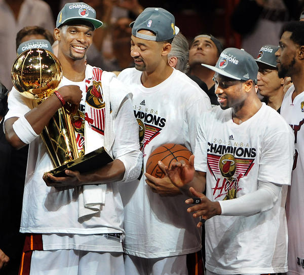 Chris Bosh holds the Larry O'Brien Trophy as Juwan Howard and Dwyane Wade look on.