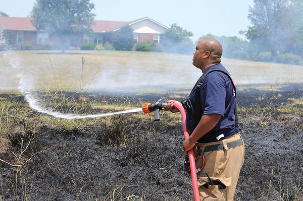 Clark County Fire Department Lt. Vince Cooper hoses down one of many grass fires that were reported on Ecton Road Thursday afternoon. Firefighters extinguished 12 to 15 different grass fires along the side of the road.