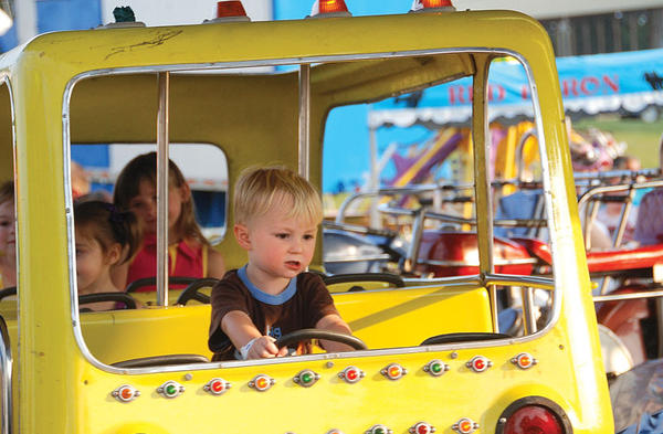Lucas Lesage, 3, takes a turn driving a school bus on one of the Paradise Amusements rides at the Clark County Fair Thursday.